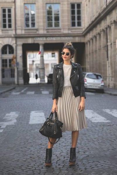 Vẻ ngoài bụi bặm nhưng vẫn rất nữ tính cùng áo khoác da và chân váy midi, thêm phần cá tính với túi xách da bản to cùng đôi boots cao cổ
