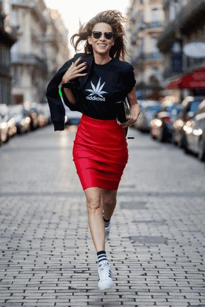 Chân váy bút chì đỏ rực rỡ kết hợp với áo phông và giày thể thao cho một set đồ năng động và hiện đại